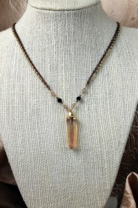 Peach quartz pendant on gold and black necklace