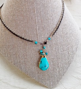 Turquoise pendant on gold and black chain